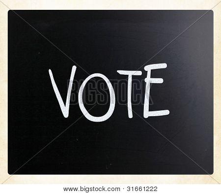 The Word 'vote' Handwritten With White Chalk On A Blackboard