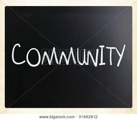"""""""comunidad"""" mano con tiza blanca sobre una pizarra"""