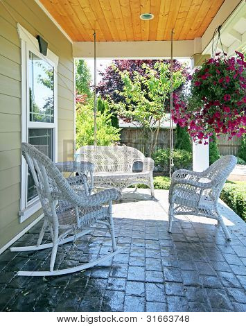 Front Porch With White Furniture And Flowers.