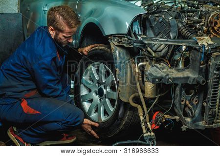 poster of Serviceman Checking Suspension In A Car At Garage. Mechanic Repaired Wheeled Vehicles. Mechanic Hold
