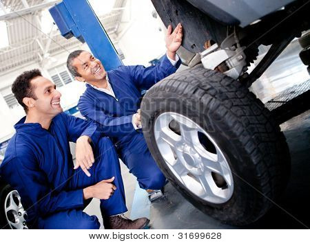 Mechanics fixing a car puncture at the garage