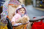 Cute Little Beautiful Baby Girl Sitting In The Pram Or Stroller On Autumn Day. Happy Smiling Child I poster