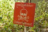 stock photo of landmines  - A plastic sign warning of landmines - JPG