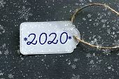 The Price Tag With The Numbers 2020, The White Tag Against The Black Wood. The Concept Of The New 20 poster