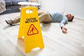 Mature Man Falling On Wet Floor In Front Of Caution Sign At Home poster