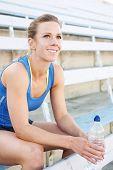 stock photo of bleachers  - Attractive blonde athlete sitting in bleachers with water bottle - JPG