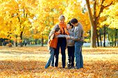 Happy family posing, playing and having fun in autumn city park. Children and parents together havin poster