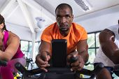 Close-up of African-american fit men exercising on exercise bike in fitness center. Bright modern gy poster