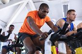 Front view of diverse fit men exercising on exercise bike in fitness center. Bright modern gym with  poster