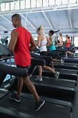 Rear view of diverse fit people exercising on treadmill in fitness center. Bright modern gym with fi poster