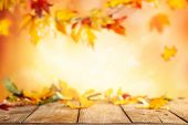 Wooden table and blurred Autumn background. Autumn concept with red-yellow leaves background. poster