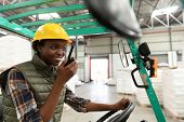 Happy female worker talking on walkie-talkie while driving forklift in warehouse. This is a freight  poster
