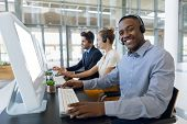 Portrait of a young African American man working in a call centre sitting at a computer wearing a he poster