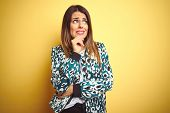 Young beautiful woman wearing casual jacket over yellow isolated background Thinking worried about a poster