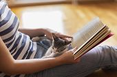 Woman Reading A Book And Holding Kitten poster