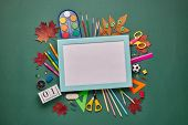 Blue frame with blank sheet and stationery accessories: pencils, pens, other office supplies on gree poster