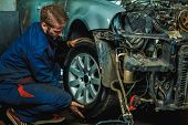 Serviceman Checking Suspension In A Car At Garage. Mechanic Repaired Wheeled Vehicles. Mechanic Hold poster