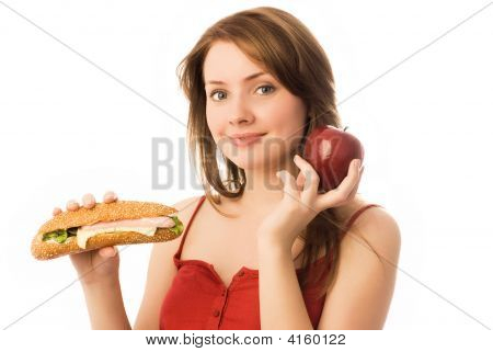 Young Woman Choosing Between An Apple And Hot Dog