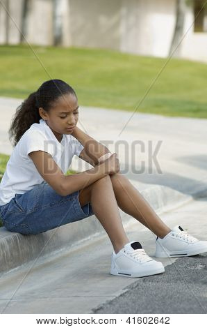 African American girl with band aid on arm sitting on curb