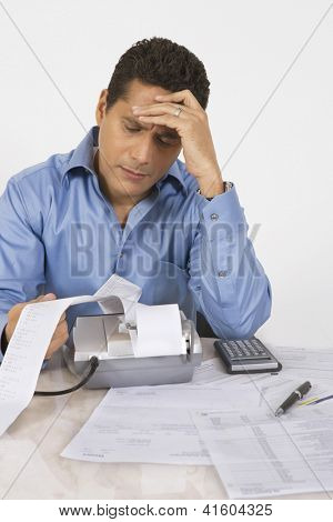Businessman with severe headache calculating finance