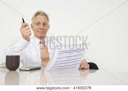 Happy businessman sitting with investment brochure at office