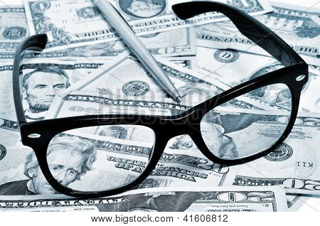 black eyeglasses and pen on a pile of dollar bills