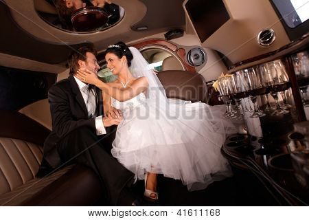 Happy couple embracing in limousine on wedding-day.