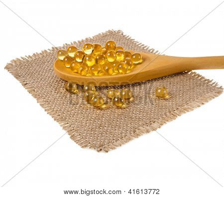 pills oil on spoon isolated on white background