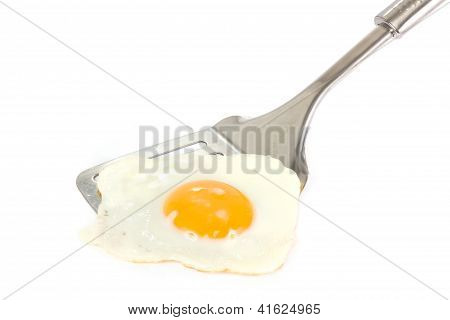 Fried Egg On A Silver Spatula Over White