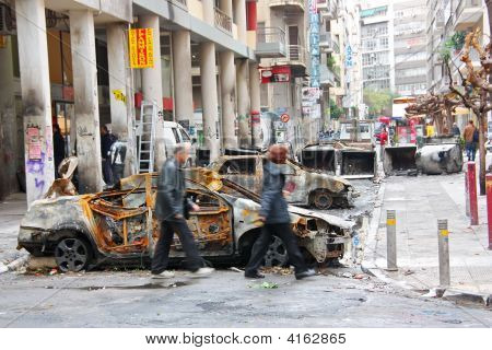 People Passing By Burnt Cars In Athens