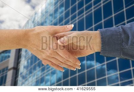 Mann und Frau Händeschütteln vor Corporate Building Hintergrund.