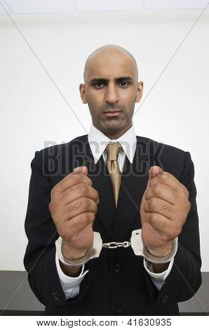 Portrait of an Indian businessman with handcuffs isolated over white background