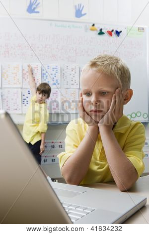 A cute preadolescent boy looking at laptop with friend pointing on whiteboard in classroom