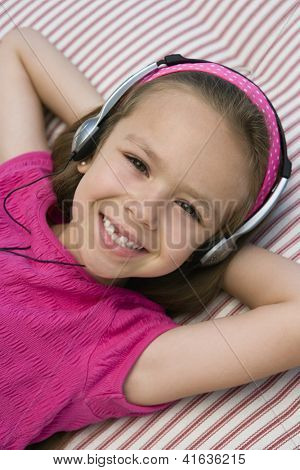High angle view of a happy preadolescent girl listening to music