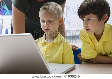 Teacher and preadolescent students with laptop in classroom