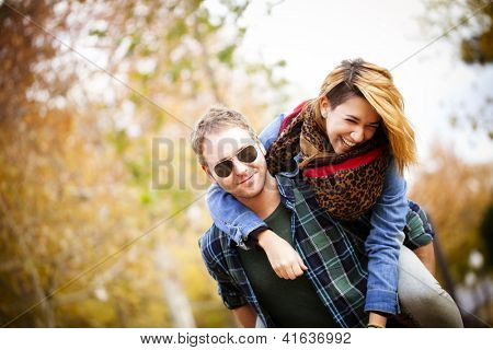 Attractive man piggybacking his pretty girlfriend outdoors