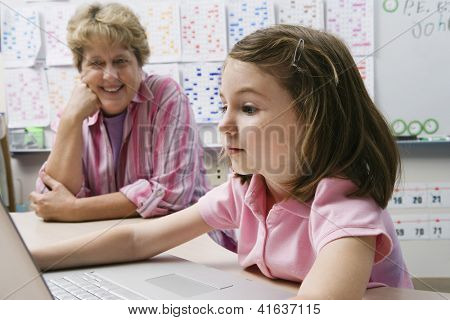 Preadolescent girl studying while teacher looking at laptop in the classroom