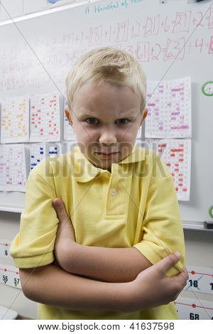 Portrait of an angry preadolescent student standing with hands folded in the classroom