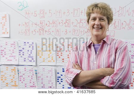 Portrait of a confident mature female teacher with arms crossed standing against whiteboard