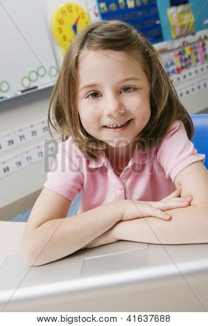 Portrait of a happy preadolescent girl sitting with laptop in the classroom