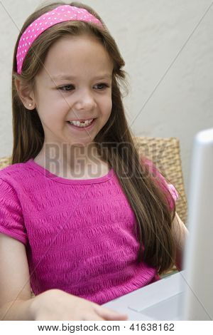 A happy preadolescent girl using laptop
