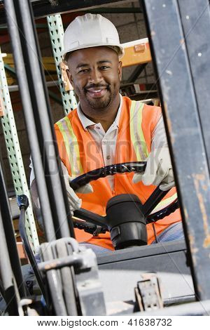 Portrait of a happy  male industrial worker driving forklift at workplace