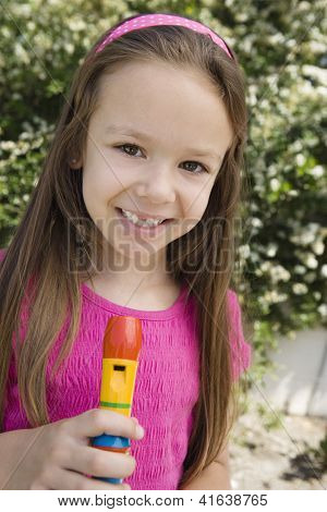 Portrait of a happy cute preadolescent girl standing with flute