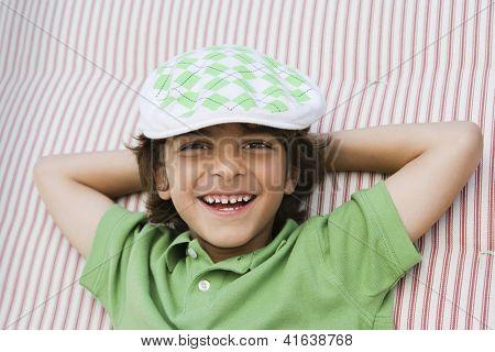 Closeup portrait of a preadolescent boy smiling on bed