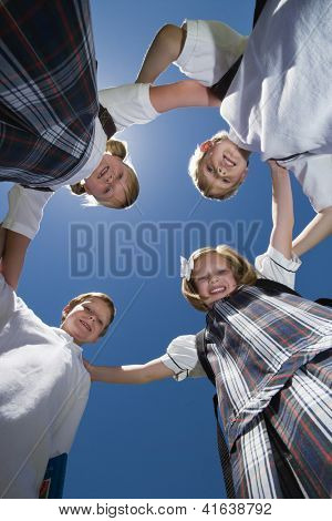 Happy school friends forming huddle together against blue sky