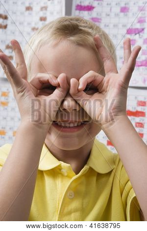 Happy Caucasian preadolescent boy looking through hand binoculars