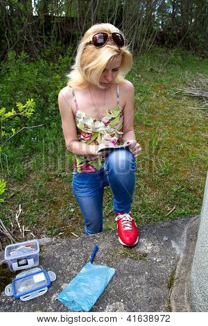 Woman Writes In Geocaching Logbook
