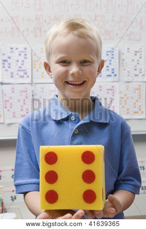 Portrait of a preadolescent boy holding yellow dice against whiteboard