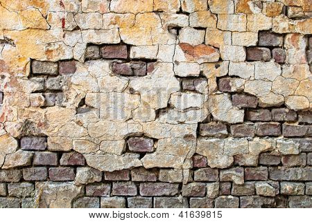Old bricks wall with cracked stucco layer background.