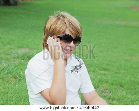 Beautiful and perky blond boy in sunglasses talking on mobile phone